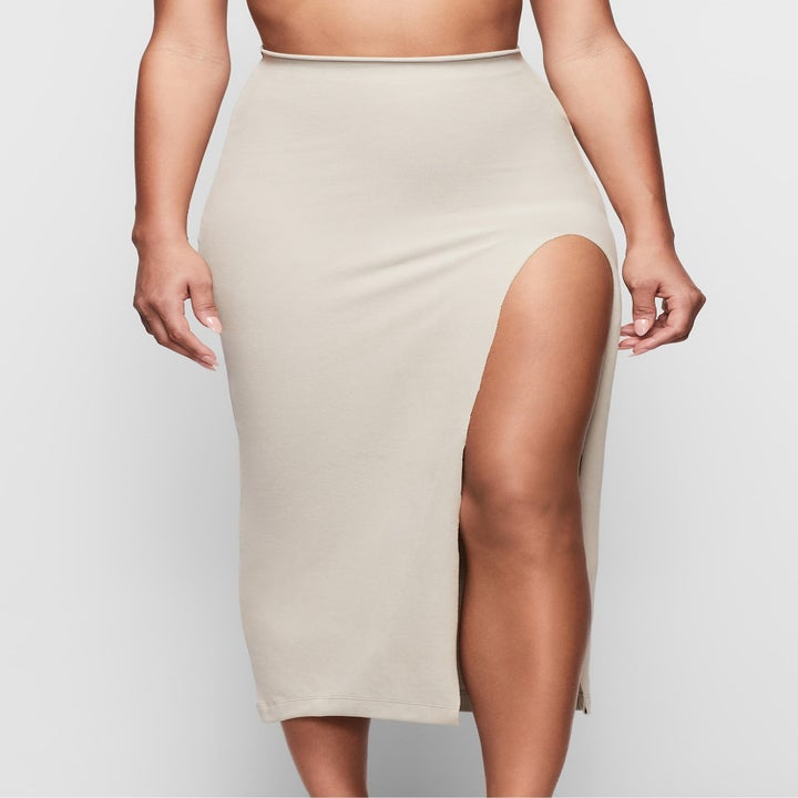 same model wearing a skirt with a high slit on one side to show the shapewear is undetectable beneath the garment