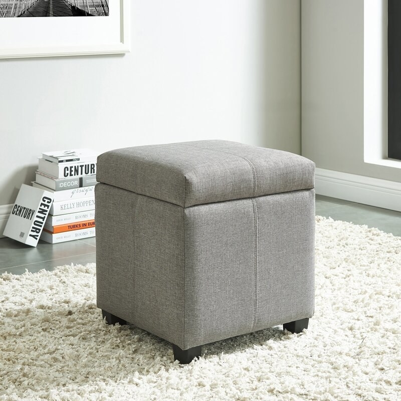 A light gray fabric square ottoman with a removable top on a textured white rug