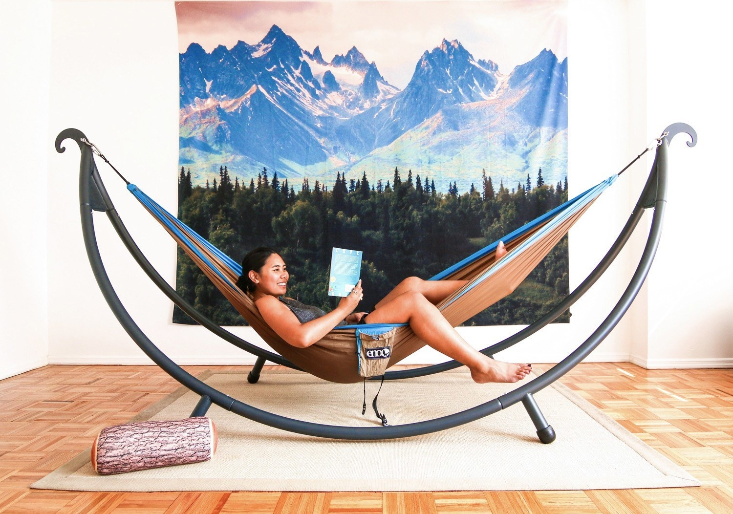 A person relaxing indoors on a hammock supported by the curved hammock stand