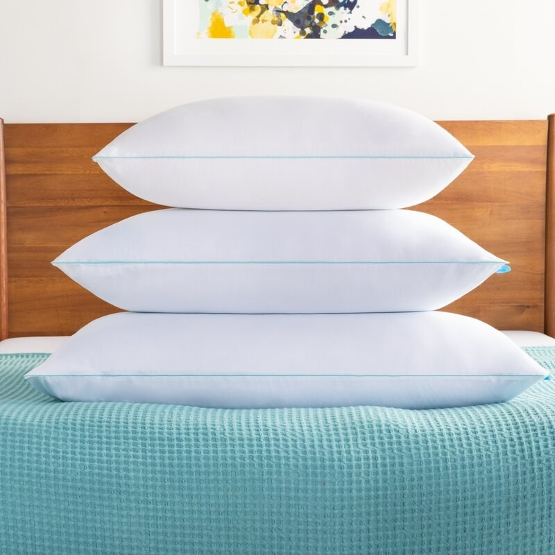 Three of the pillows stacked on a bed