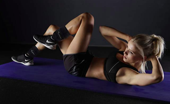 A toned woman lays on a yoga mat doing twist crunches while wearing ankle weights