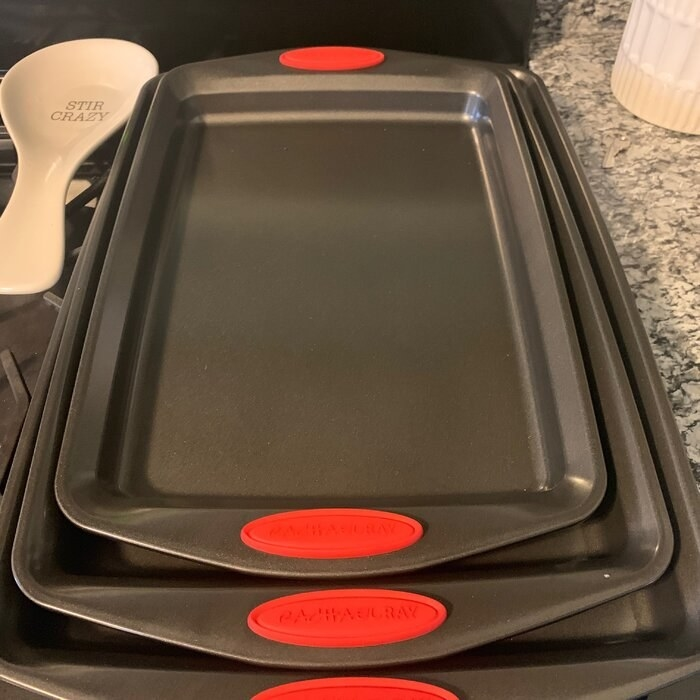 Three dark gray metallic cooking sheets nested within each other with a red rubberized Rachael Ray logo on each of them