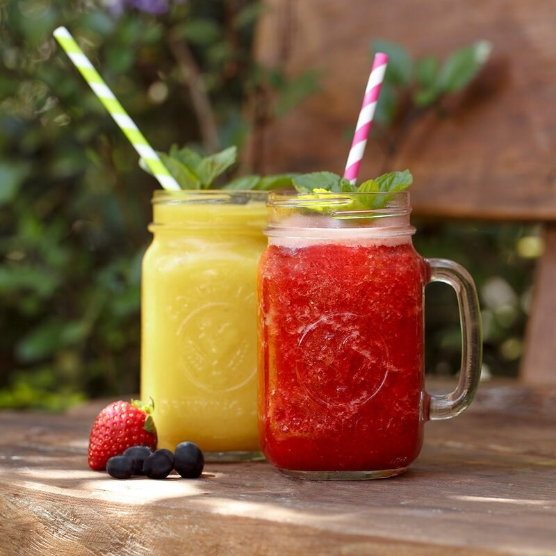 Two frosty mason jar glasses filled with colorful icy drinks atop an outdoor table