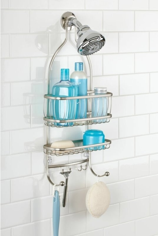 A metallic two-shelf shower caddy holding soap and containers while hanging from a shower head with four sets of hooks for razors and sponges