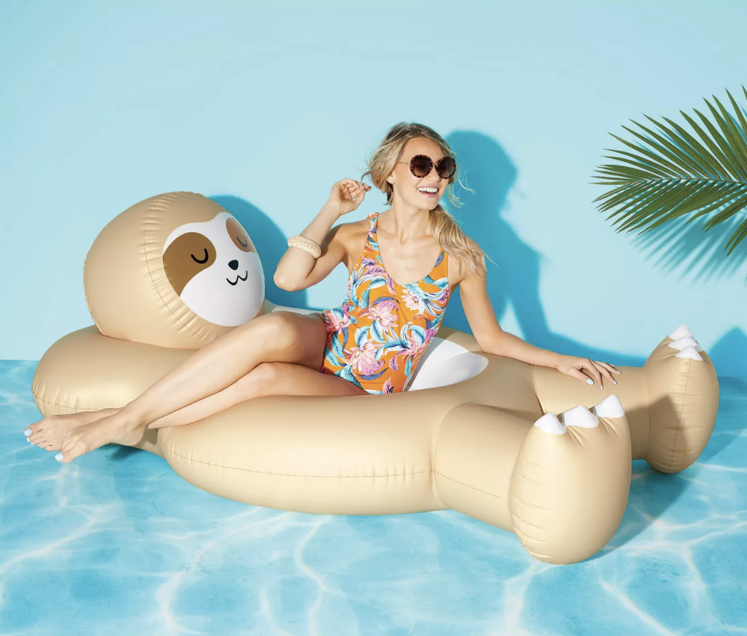 a person in a bathing suit sitting in the middle of an oversized sleepy sloth pool float