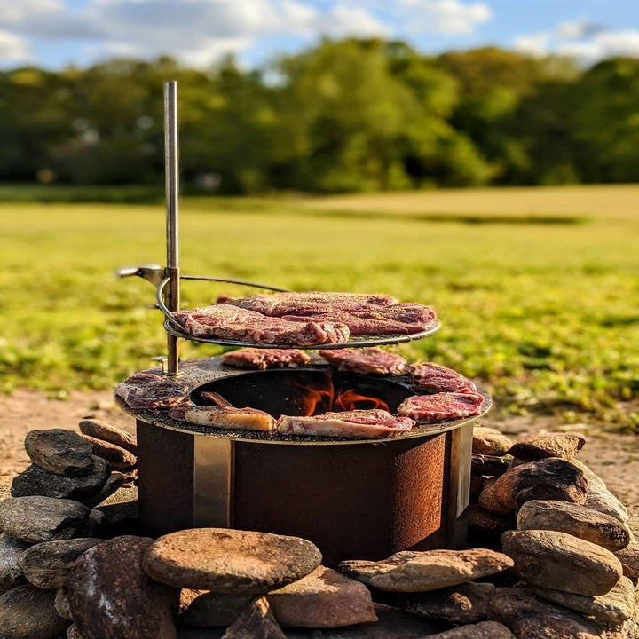 a copper colored circulate fire pit surrounded by stones with a grill piece attached to the side with meat on top of it