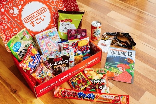 The box overflowing with Japanese snacks like chips, ramen, beverages, and candy