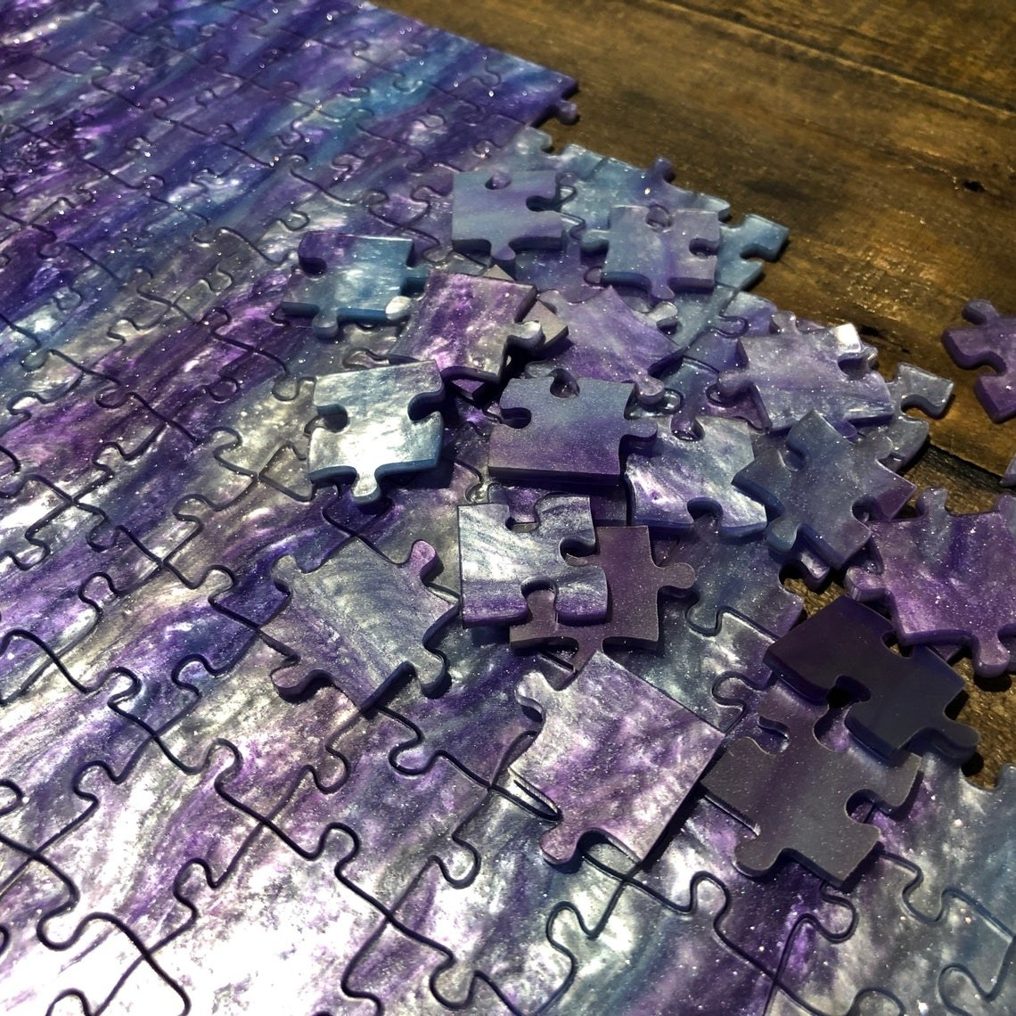 holographic purple and silver jig saw puzzle with some connected and some loose pieces. No decipherable patten on puzzle, so it would be difficult
