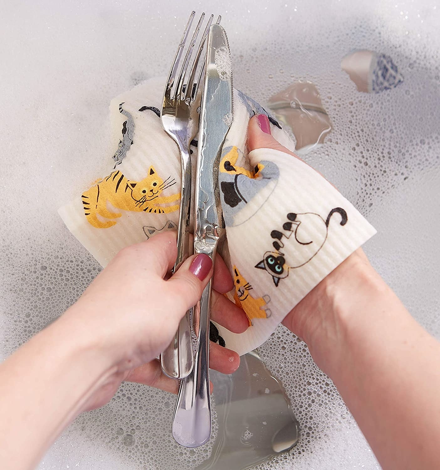 A person washing a knife and fork with a  Swedish dish cloth with happy cats printed on it