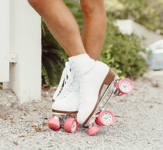 A closeup of a woman wearing white roller skates with pink wheels