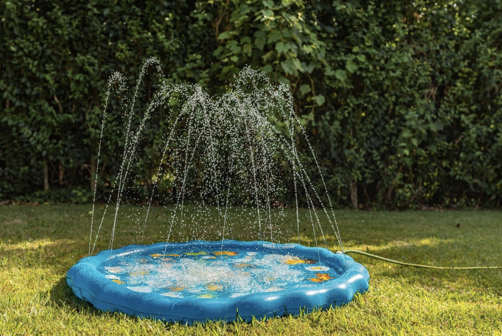 A circular waterproof pad with holes all around it for water to spout out of once someone installs a hose into it