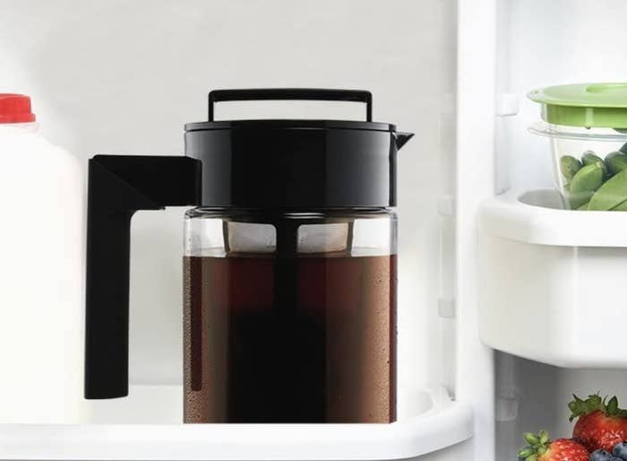 A pitcher with a coffee filter and a large handle, full of iced coffee in a fridge