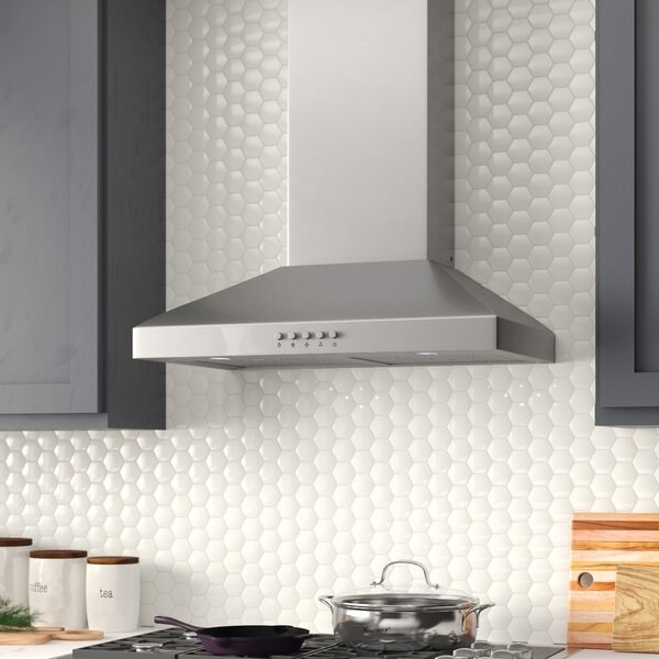 kitchen scene with part of stove visible and white tile backsplash. Main focus is sleek contemporary silver range hood with buttons on the front