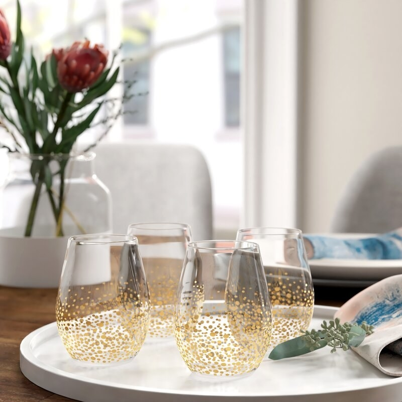 The set is sitting on a tray. They've got gold flecks (like differently sized polka dots) starting from the bottom of each glass and stopping near the midway point.