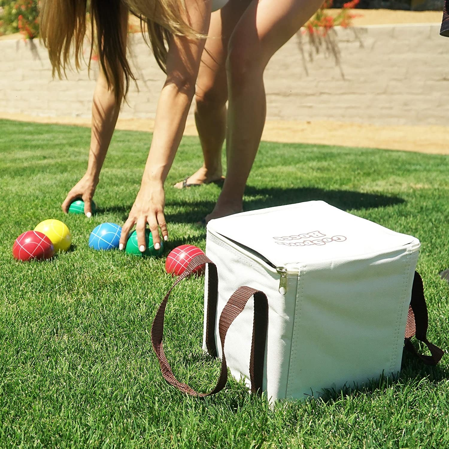 a person bending down in grass to pick up red, green, yellow, and blue bocce balls next to a white zippered square case to hold the balls in