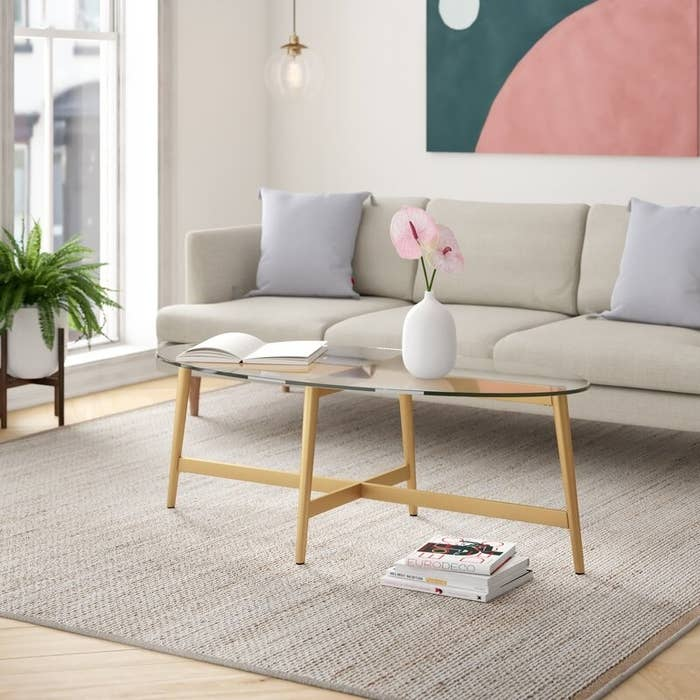 A glass oval coffee table on wooden legs