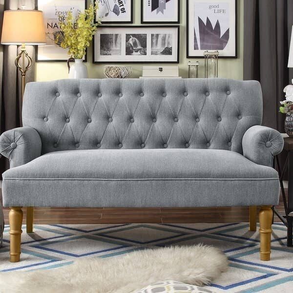 gray upholstered settee with turned maple legs, rolled arms, and enough room for about two people to sit on it.