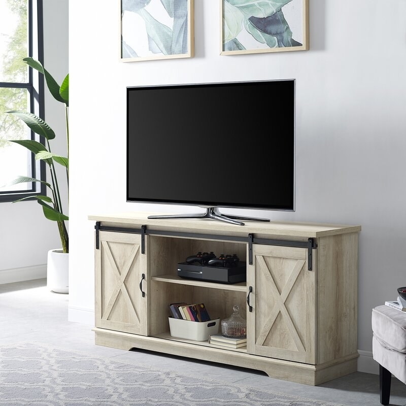 A rectangular television stand with an open space for two shelves in the middle and two mirroring cabinets on either side for storage, staged in a living with with a television on top of it