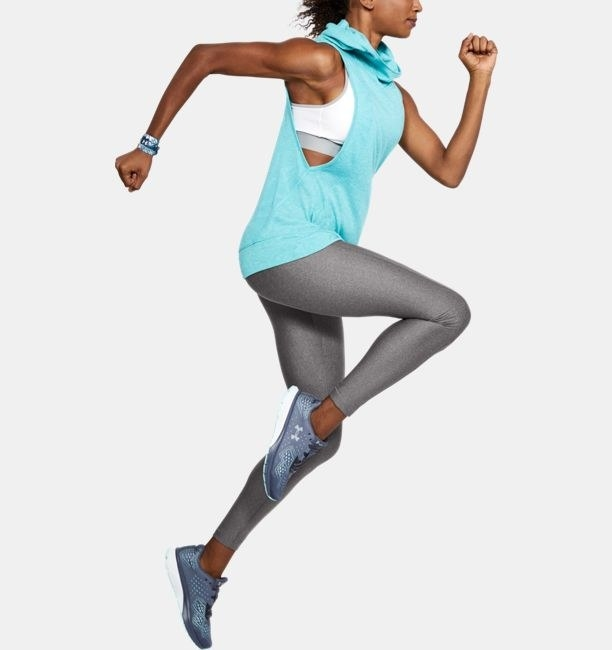 A toned Black woman wearing the leggings in metallic silver sprinting in mid-air