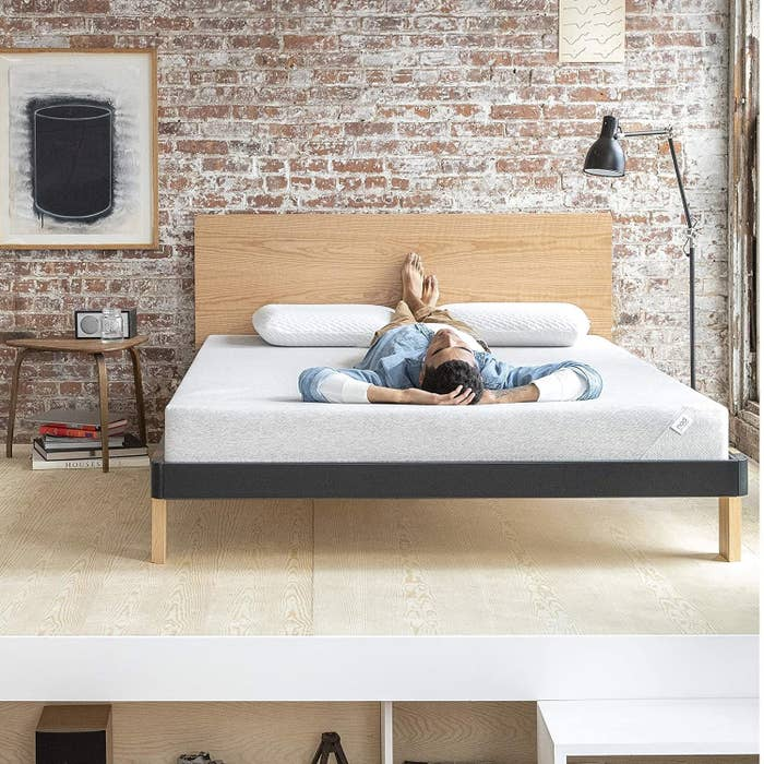 The Nod Adaptive Foam mattress staged in a room with a model reclining on top