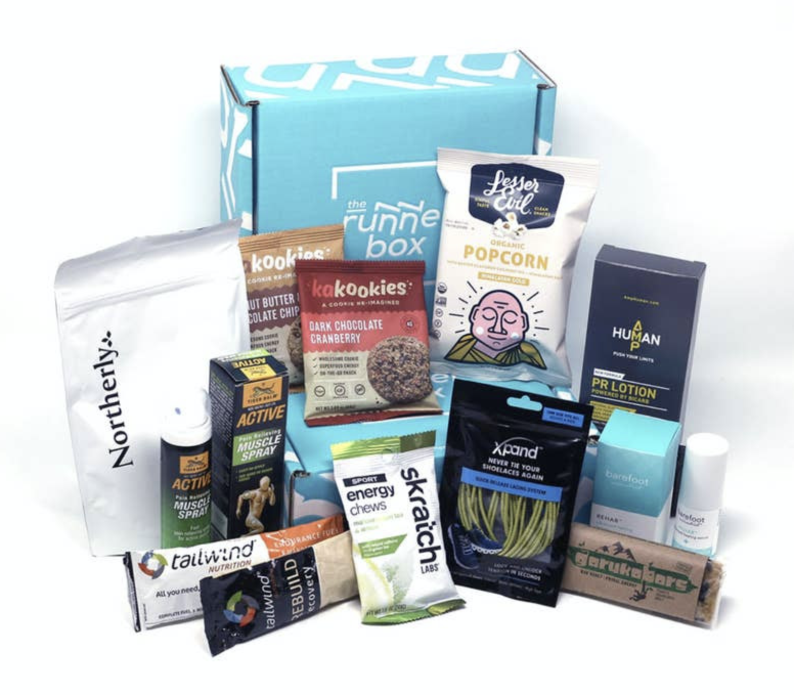 "A blue box that says ""The RunnerBox"" with snacks and running accessories in front of it including a white package that says ""Lesser Evil Organic Popcorn"" and a bottle that says ""Tiger Balm Active Muscle Spray"""