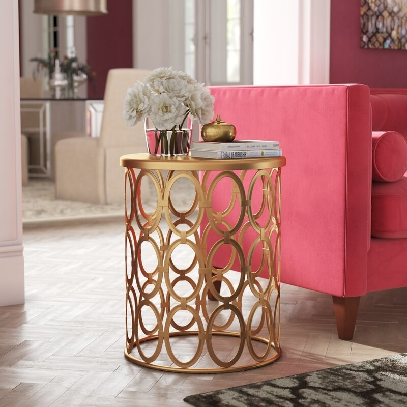 A cylinder-shaped gold end table with metal circles all around the base holding up the top, with books and flowers on top