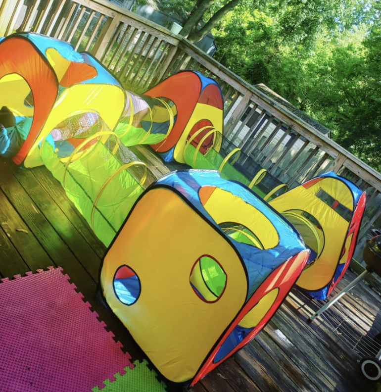 an outdoor tunnel system for kids featuring a bunch of primary colors