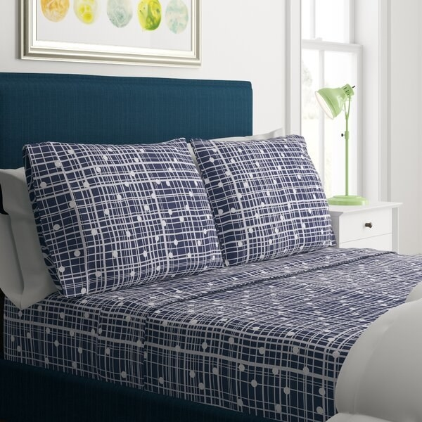 bed with sheets and pillowcases visible covered in a grid-like pattern that has polka dots on it