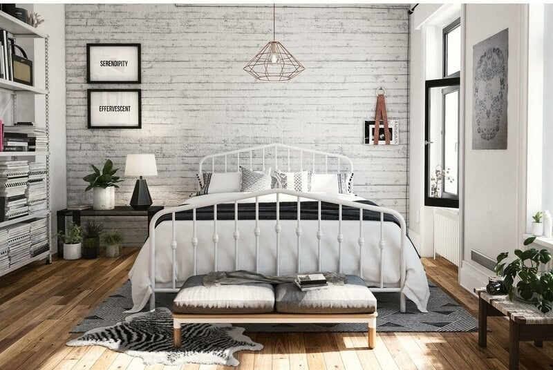 A bedroom with a bed propped on a white-painted platform bed frame with spokes with round finials in the middle of them