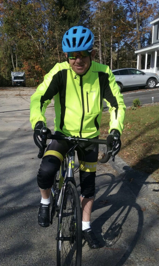 A reviewer wears a neon yellow reflective jacket while bike riding on a street