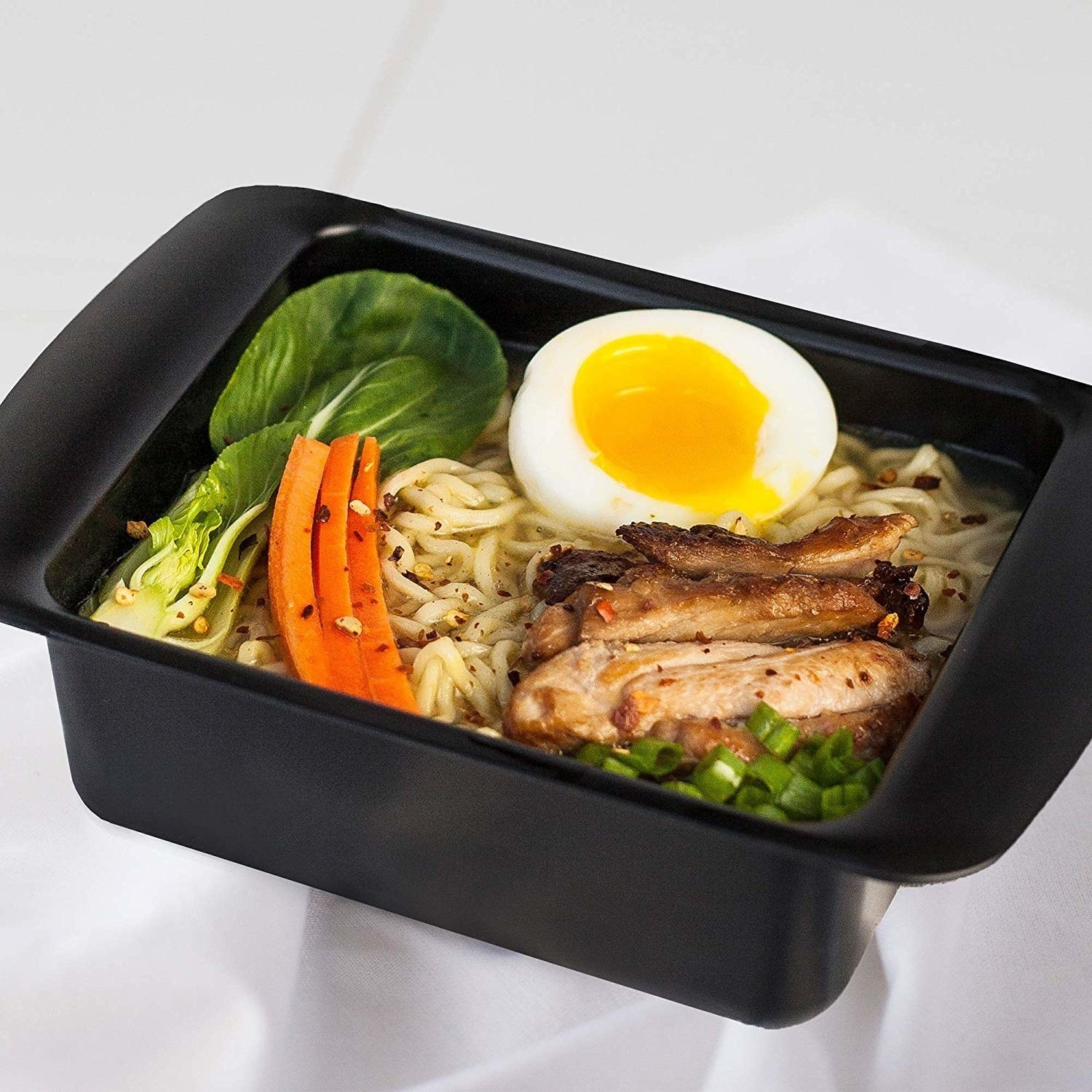 black ramen cooker with noodles, hard-boiled egg, scallions, and carrot inside