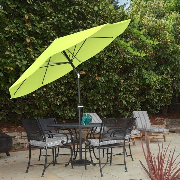 patio view with a round table and four chairs with an umbrella that'll fit into the table. The umbrella is large and tilted to adjust for the sun