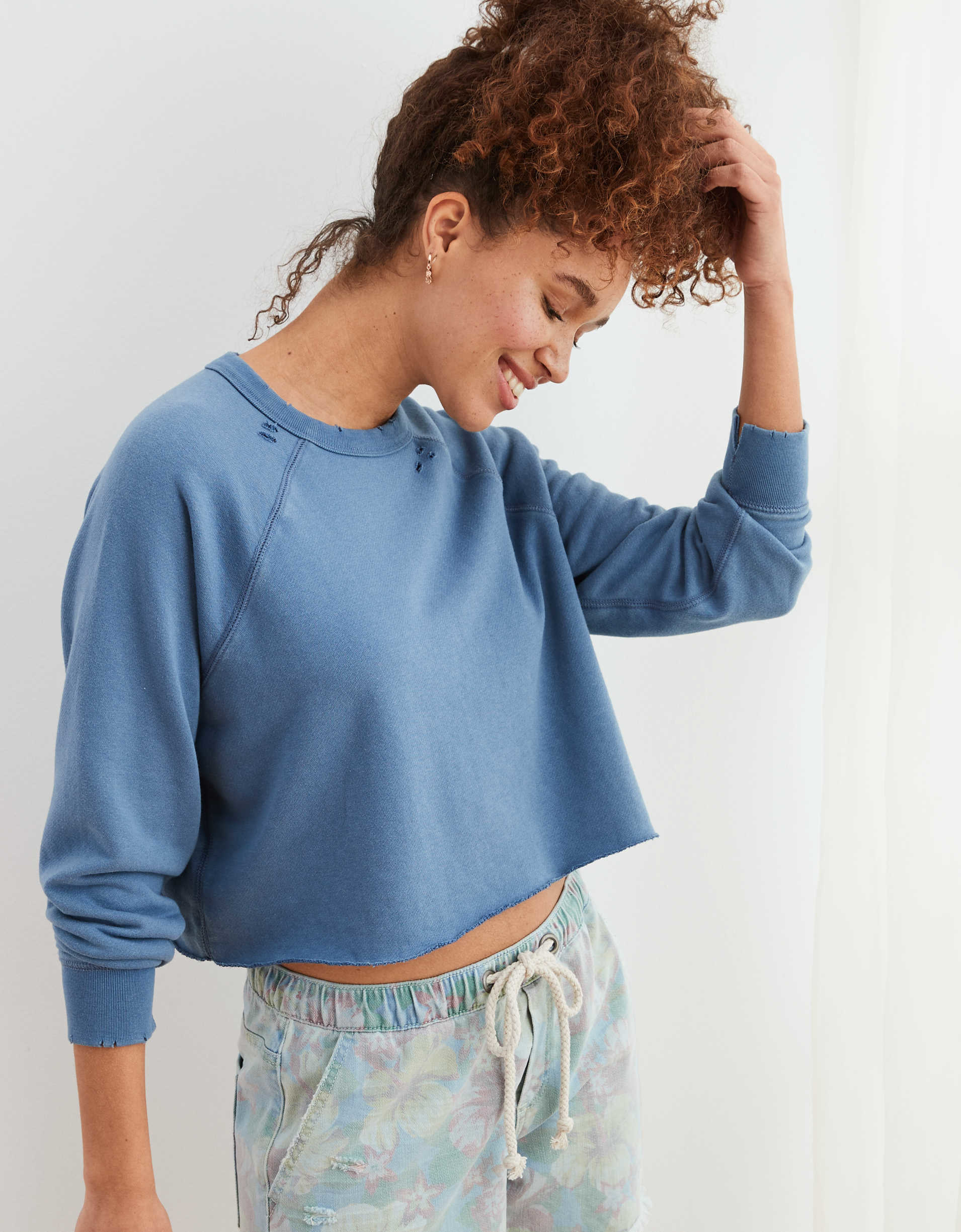 model in a slightly cropped blue crewneck sweatshirt with tiny holes near the beck and wrists