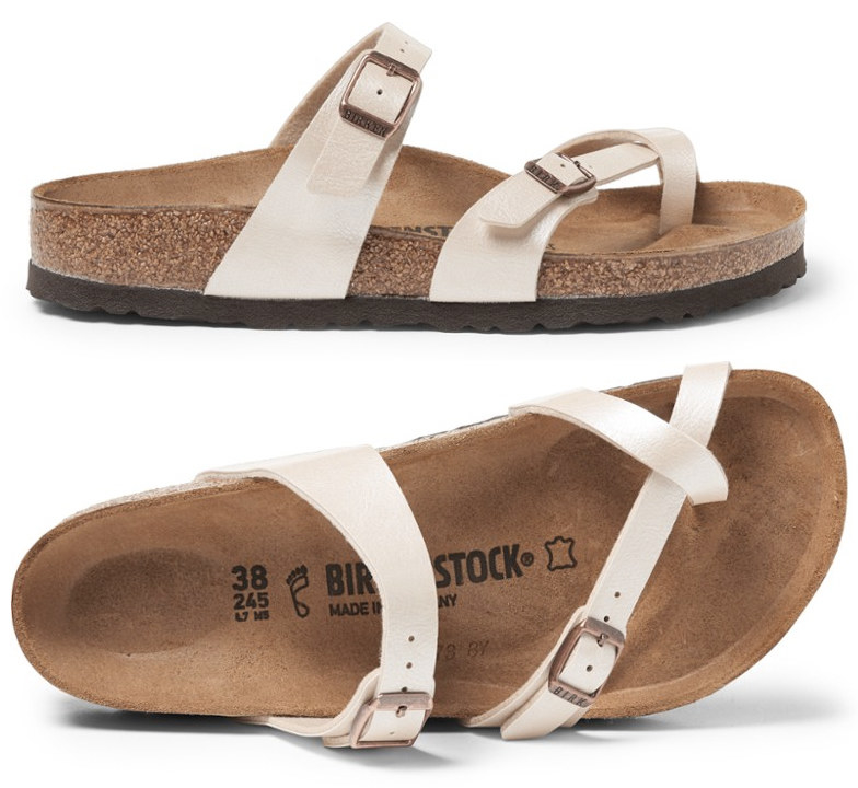A three-strap, two-buckle white Birkenstock shoe with brown footbed; one strap goes across the top of your foot near your ankle; another goes across just below your toes, and a third goes across only your big toe.