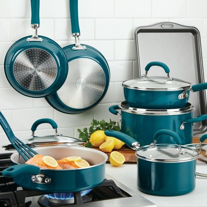A turquoise cookware set with a variety of pot and pan sizes