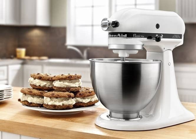 A white KitchenAid stand mixer next to a plate of baked treats