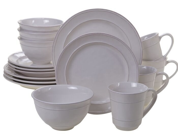 A white rustic-looking dinnerware set made up of salad plates, dinner plates, bowls, and mugs
