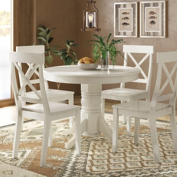 dining room area with white wood table set of a round pedestal table with four chairs around it