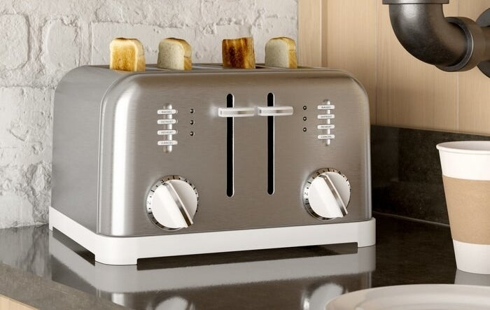 A toaster holding four pieces of bread all at varying toast levels