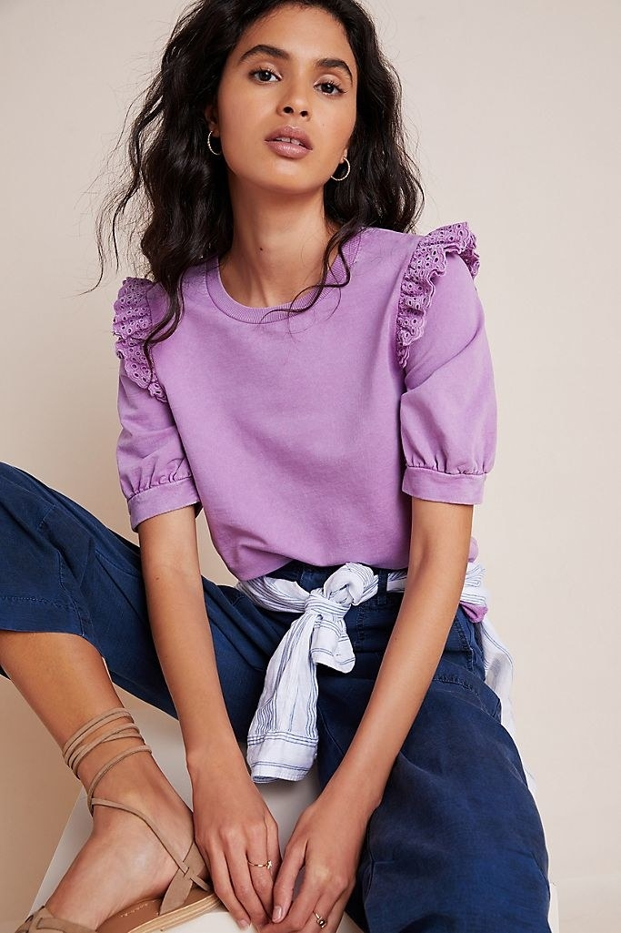 A model wearing the ruffled eyelet pullover in violet.