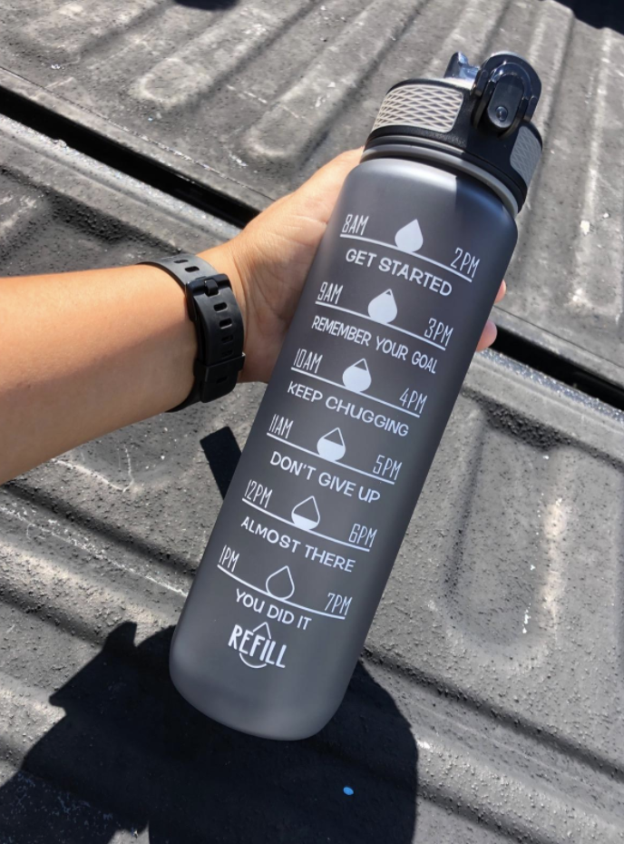 A reviewer holds a gray time-marked water bottle