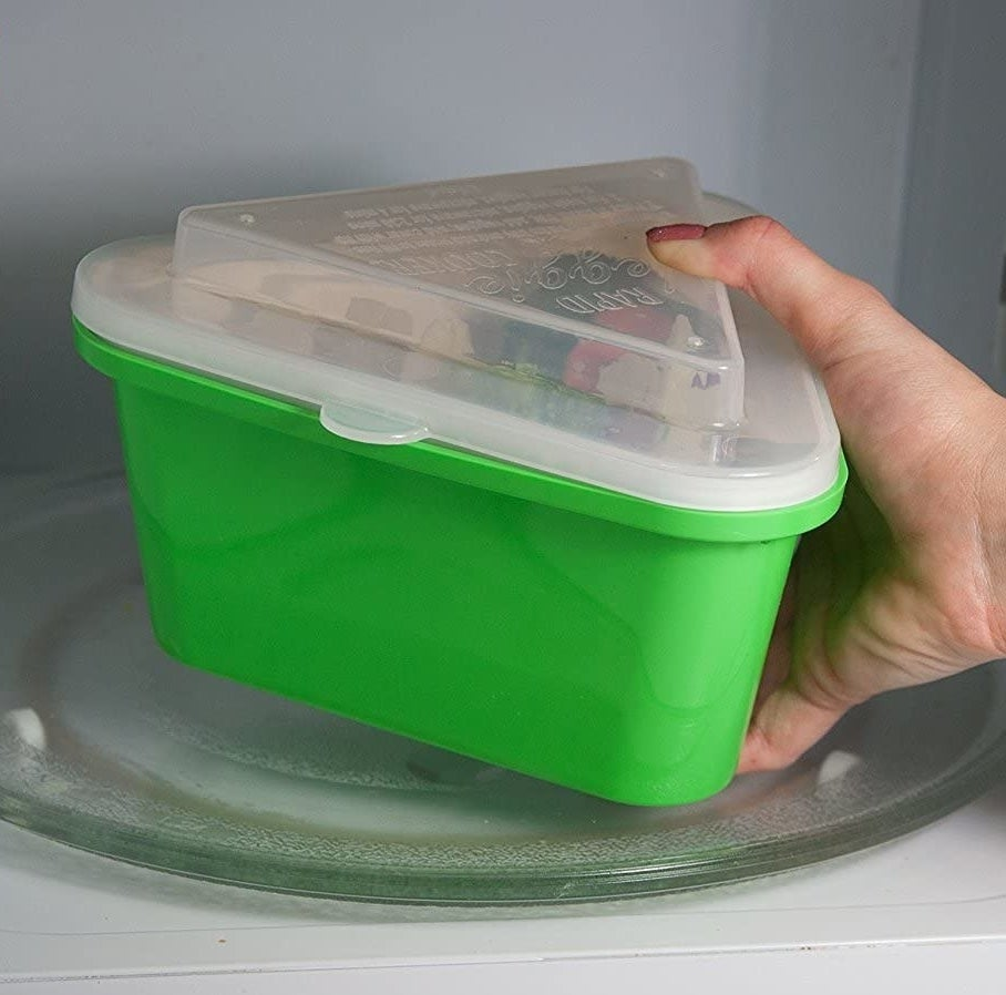 hand holding green steamer with clear plastic cover