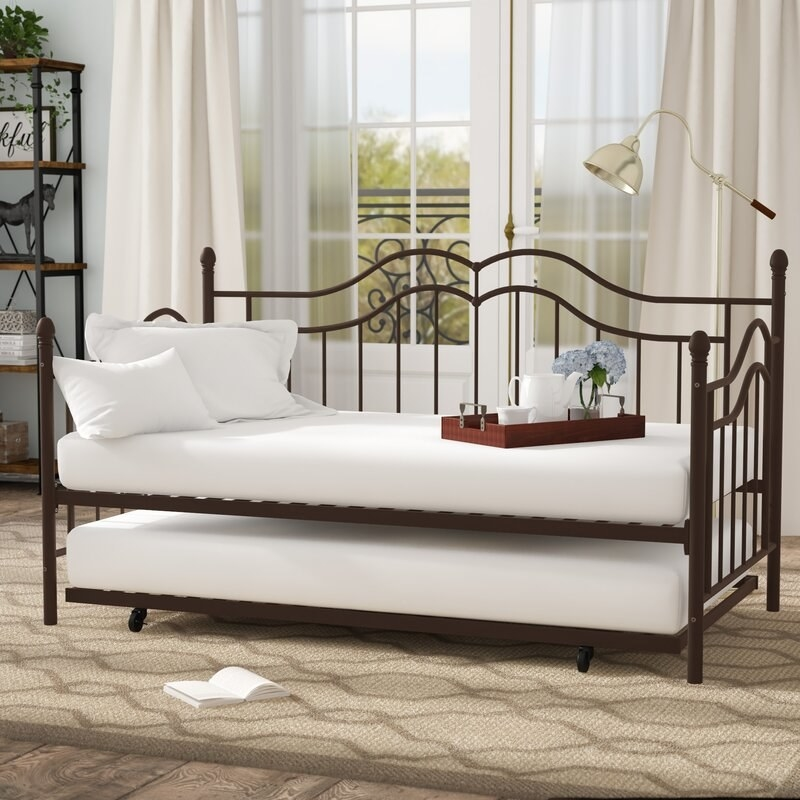 A twin sized day bed with a metal frame with one mattress on top and a second frame underneath it that can slide a second mattress out as well