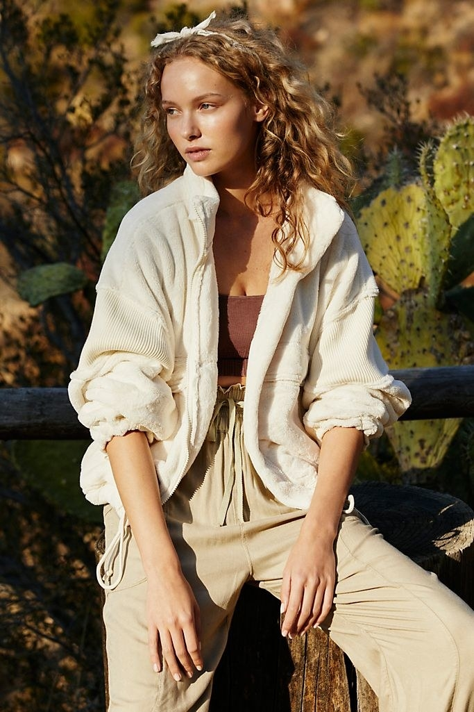 A model wearing the Free People Movement fleece jacket in vintage white.