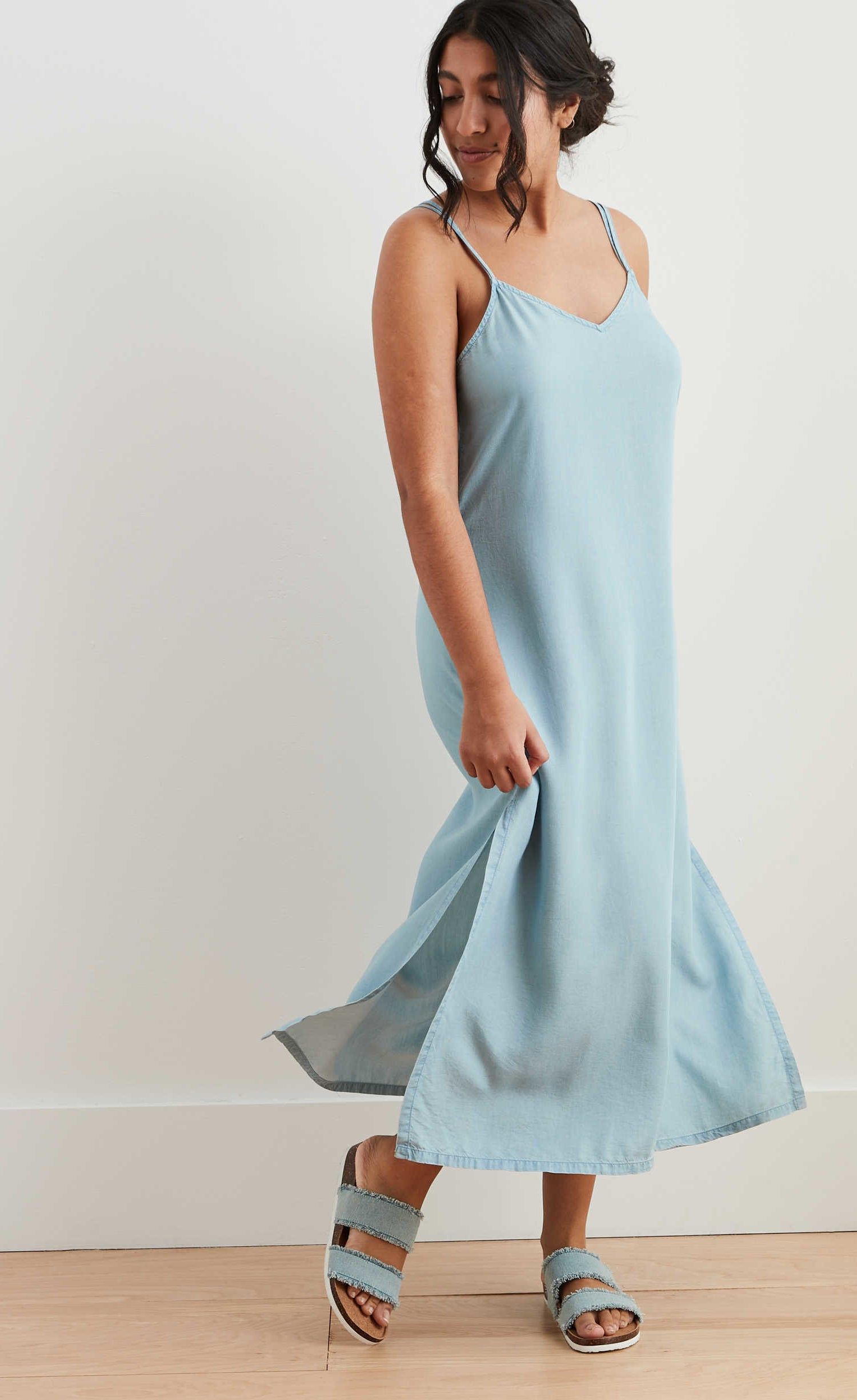model in midi length chambray slip dress with spaghetti straps and slits up to the knee on either side