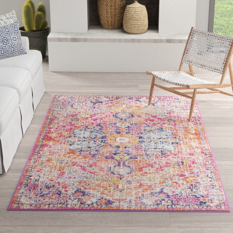 A large rug on the floor of a living room with a Persian-inspired, distressed pattern in bright colors