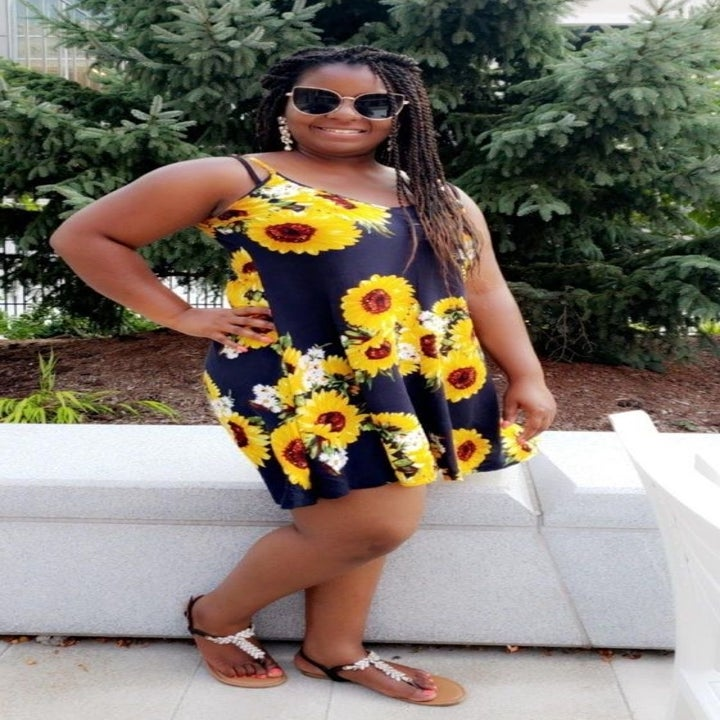 Reviewer wearing the black and yellow sunflower spaghetti strap dress in size large