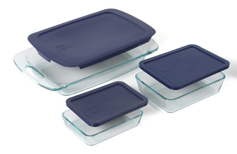 Three rectangular glass baking dishes with dark blue snap tops floating above them