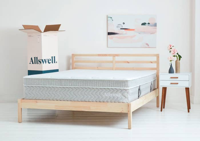 A bed-in-box mattress with a plush top in gray on a wooden bed frame next to the box it came in