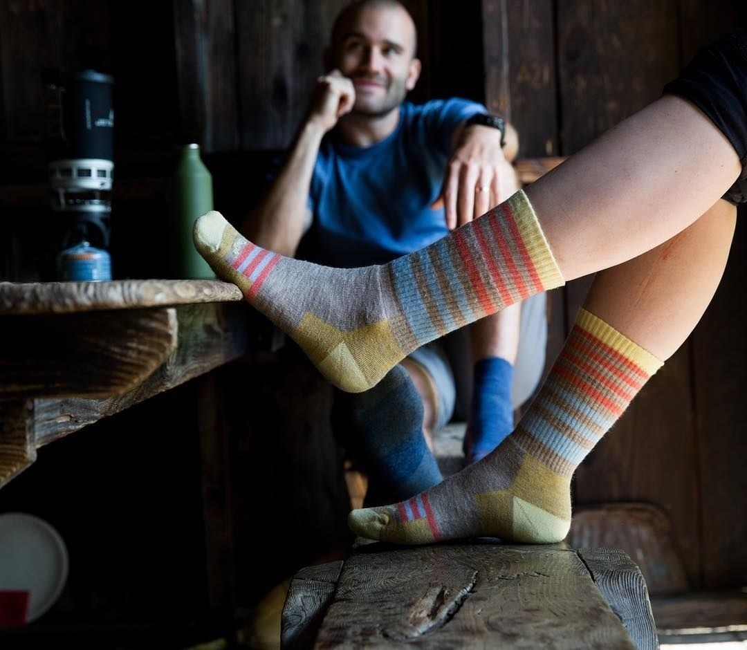 A pair of feet resting on a picnic table wearing the crew-height socks with stripes. Although the exact color is no longer in stock, they're grey with blue and orange stripes, and yellow-green on the heels and toes